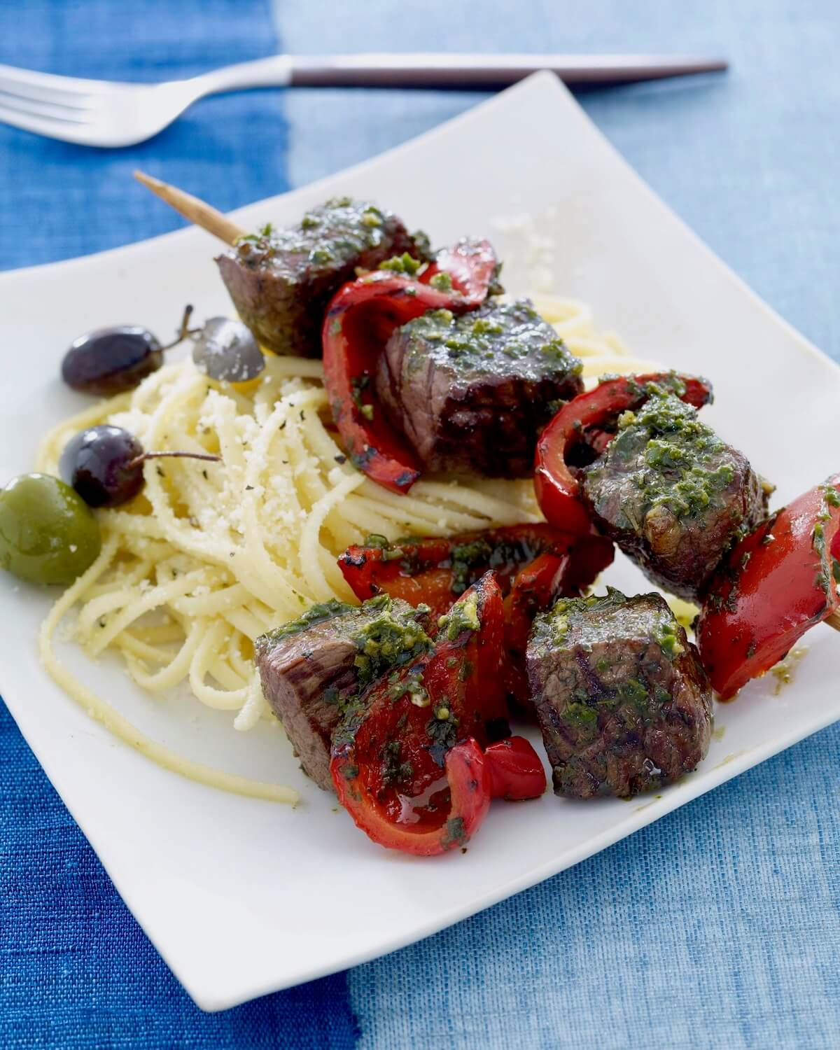 grill steak kabobs with pesto on white plate with pasta