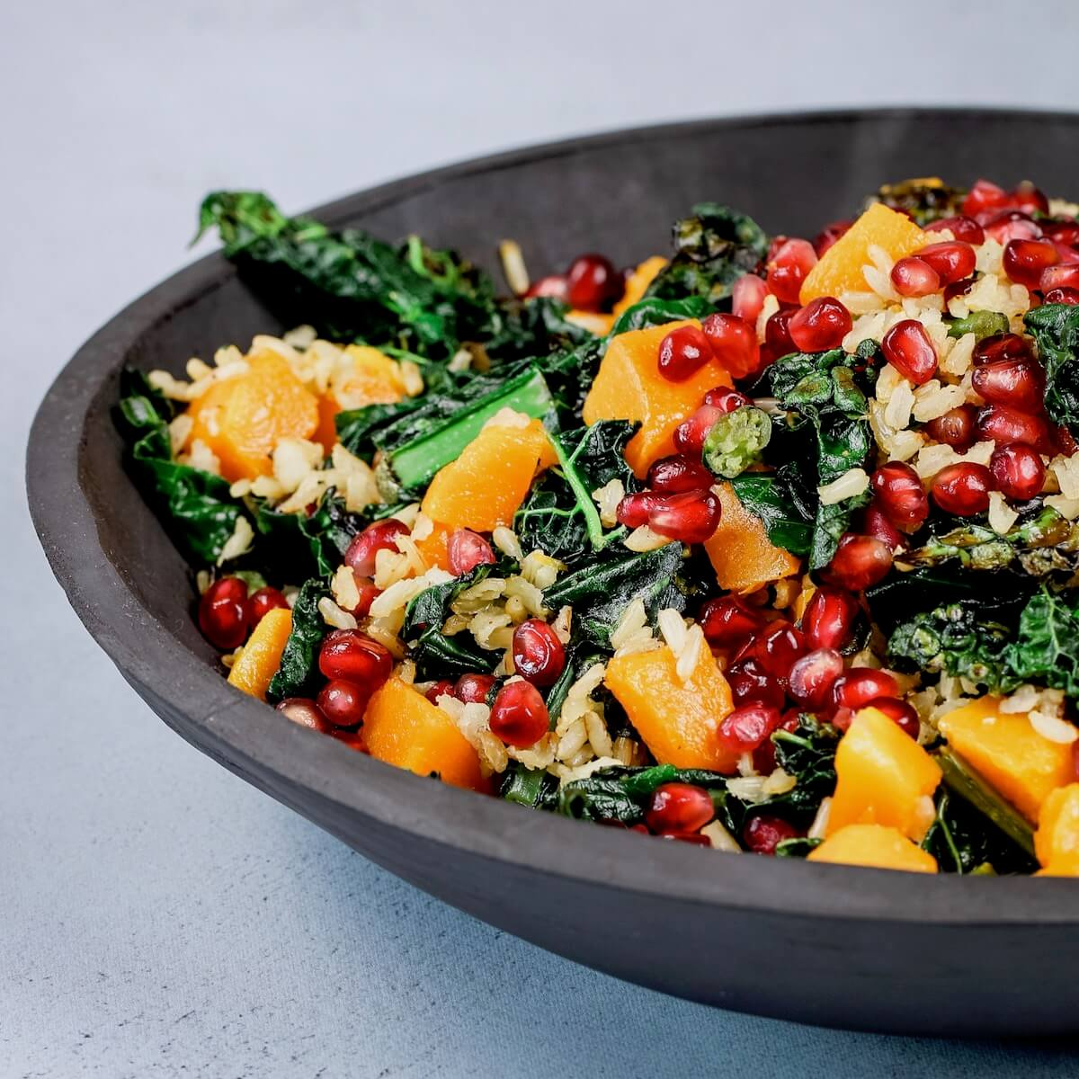 kale and squash salad with brown rice and pomegranates in a slate bowl feature