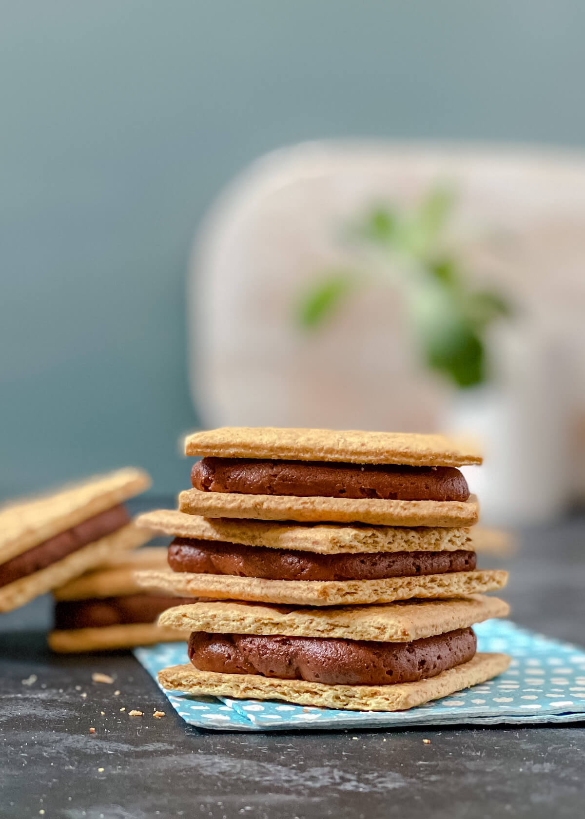 graham crackers stacked on a napkin with chocolate frosting filling