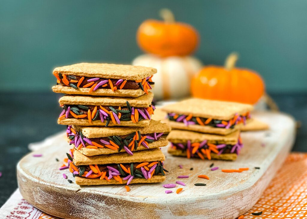 stack of graham crackers filled with chocolate frosting and purple and orange sprinkles