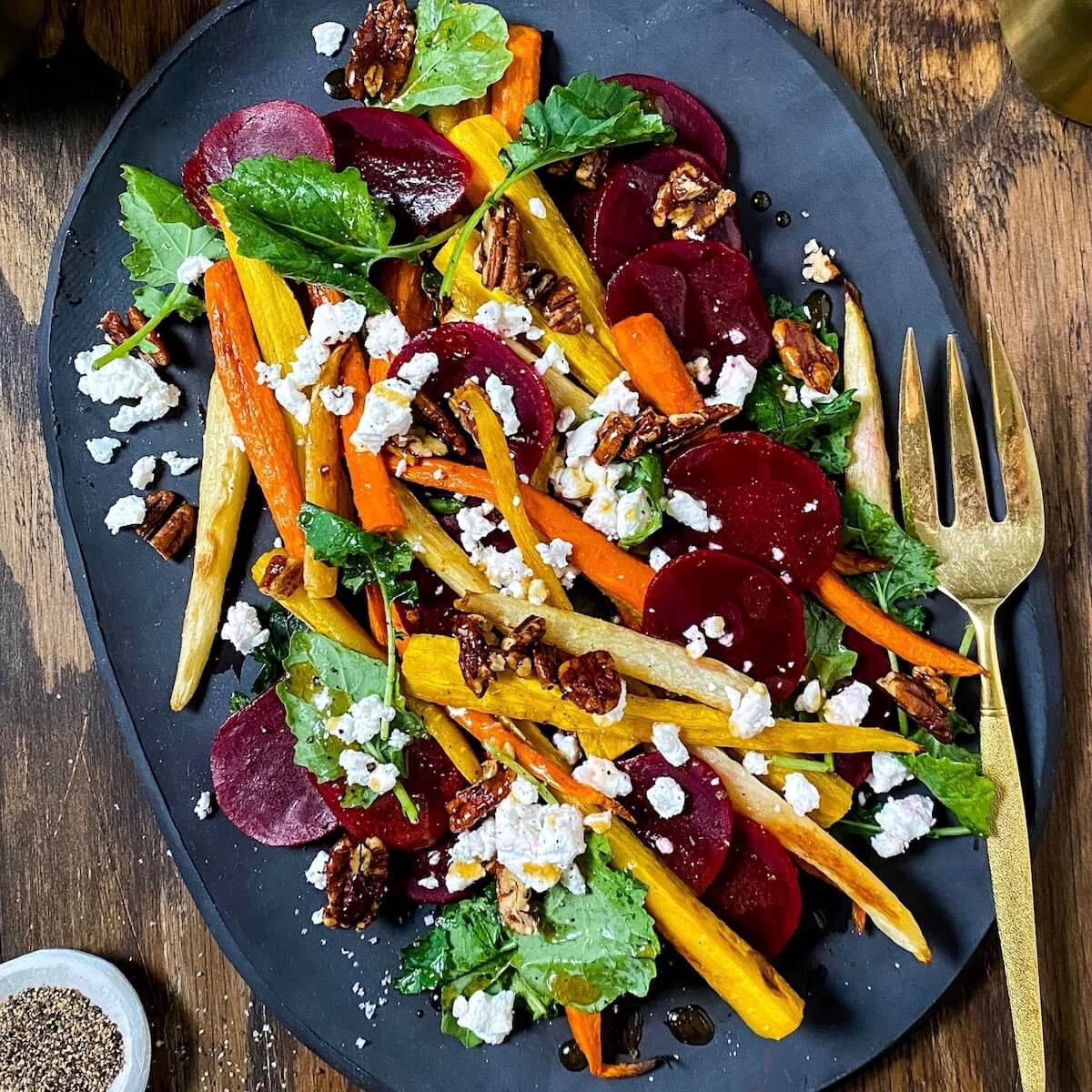 kale and beets with roasted carrots and goat cheese on a black platter