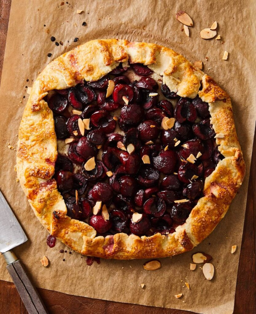 cherry crostata with almonds on brown parchment