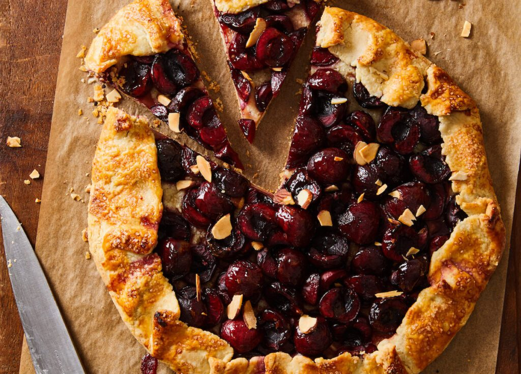 rustic cherry pie with almonds on cutting board