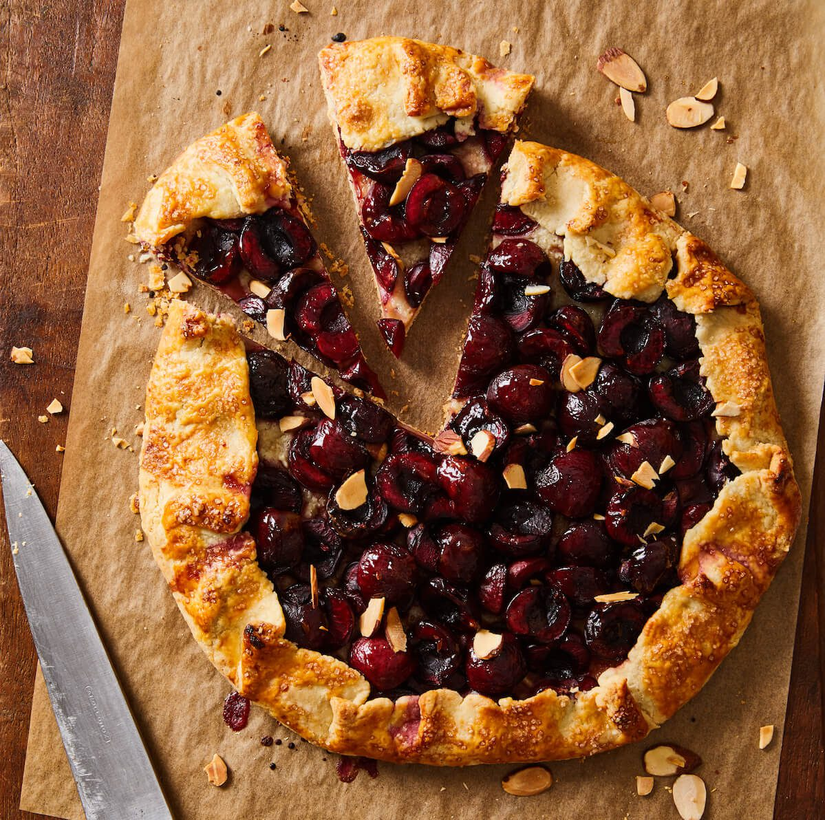 cherry galette on brown parchment with slice out