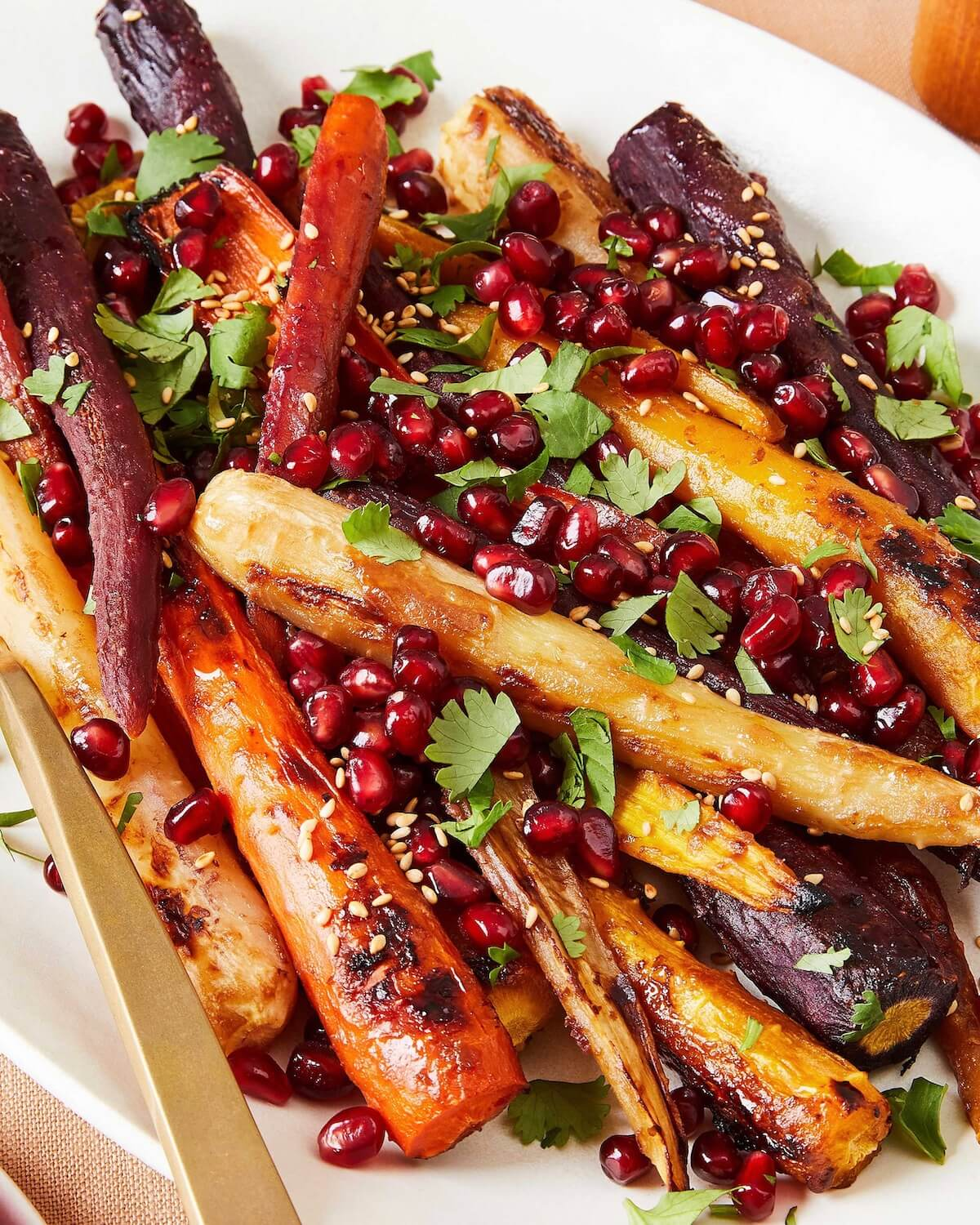 close up of roasted carrots with miso and pomegranate arils