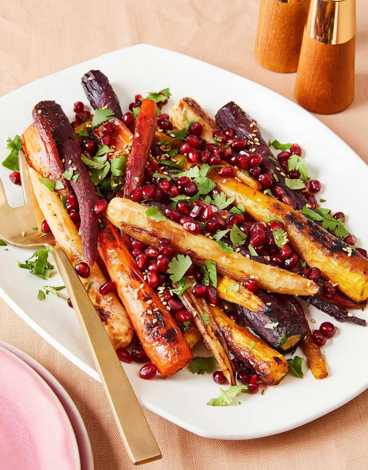 miso roasted carrots with pomegranates on white platter