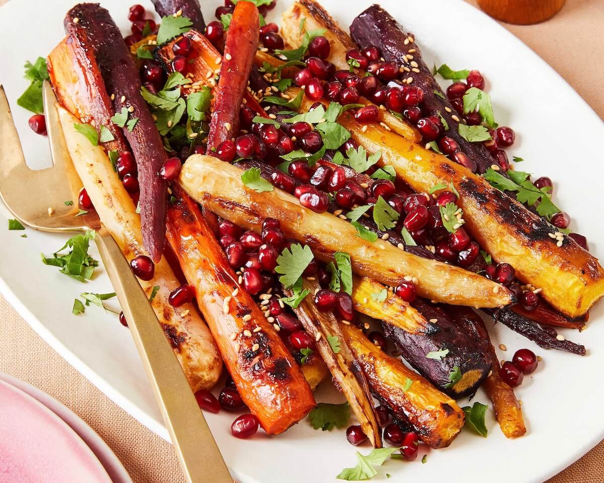 tricolor carrots on a white platter with pomegranates