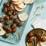 glazed meatballs with bread slices on a platter