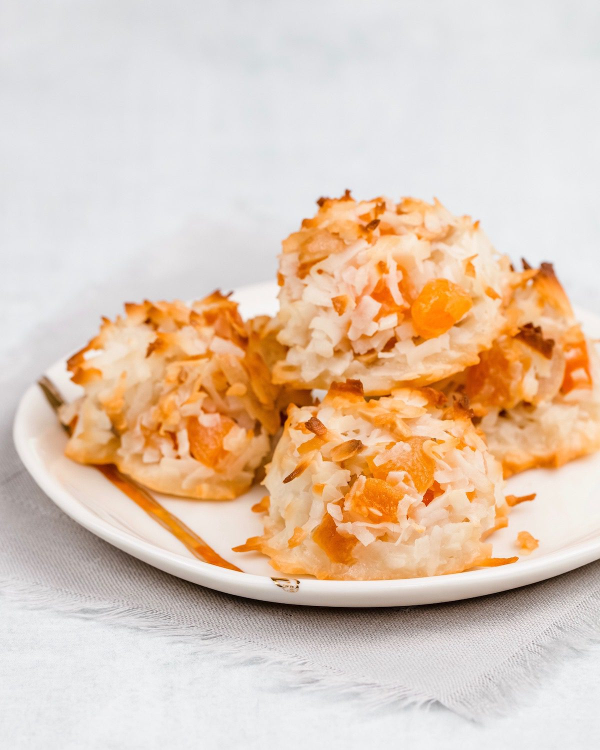 coconut macaroons with apricots on a white plate