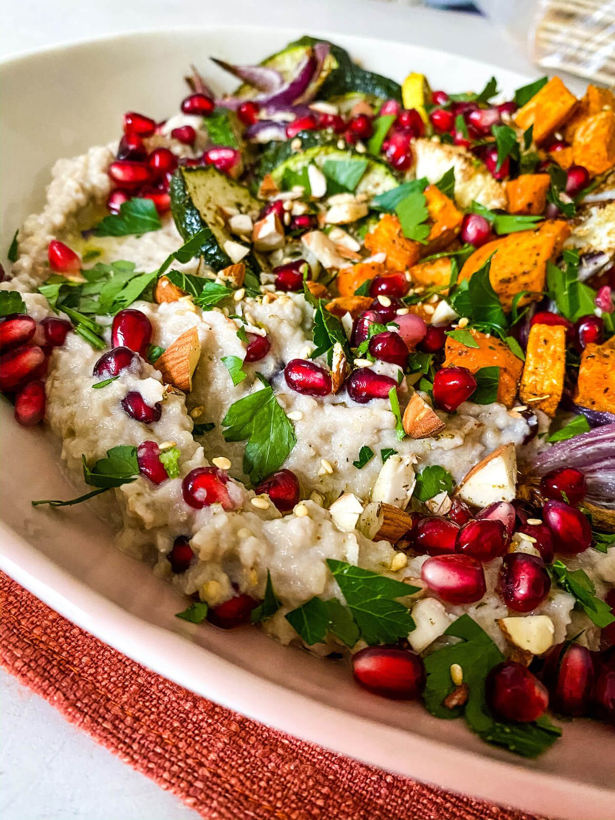 close up of baba ghanoush dip with roasted vegetables and pomegranates