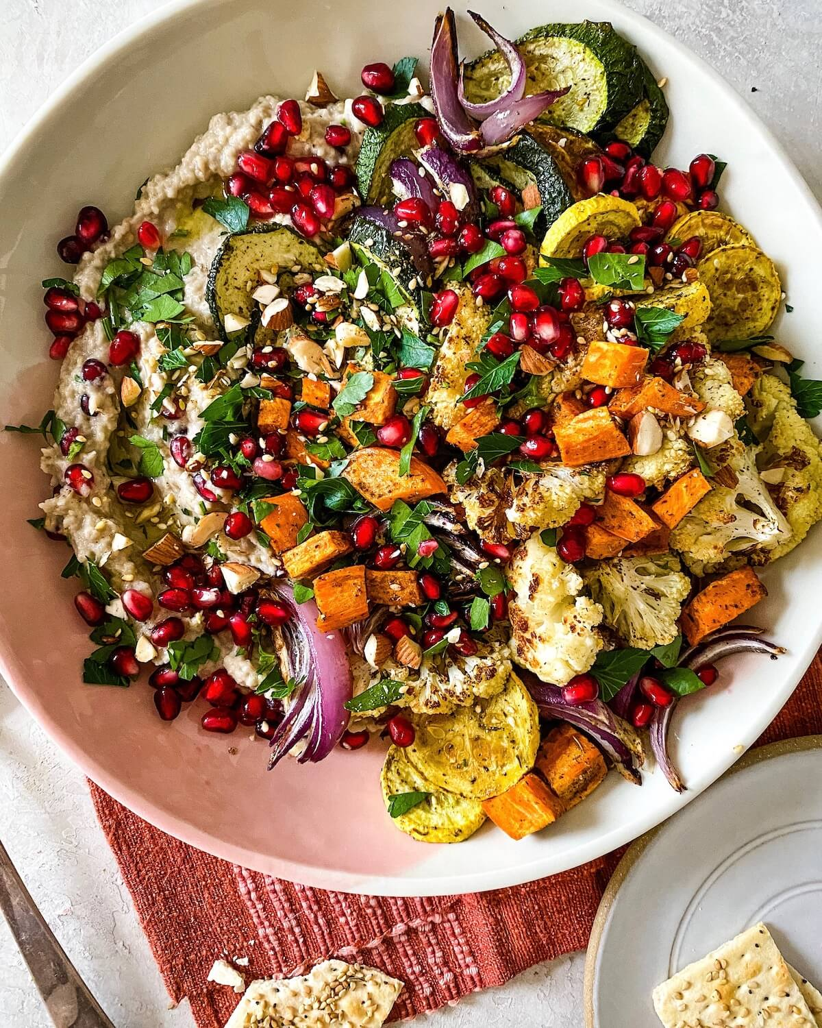colorful roasted vegetables on top of eggplant dip with pomegranates