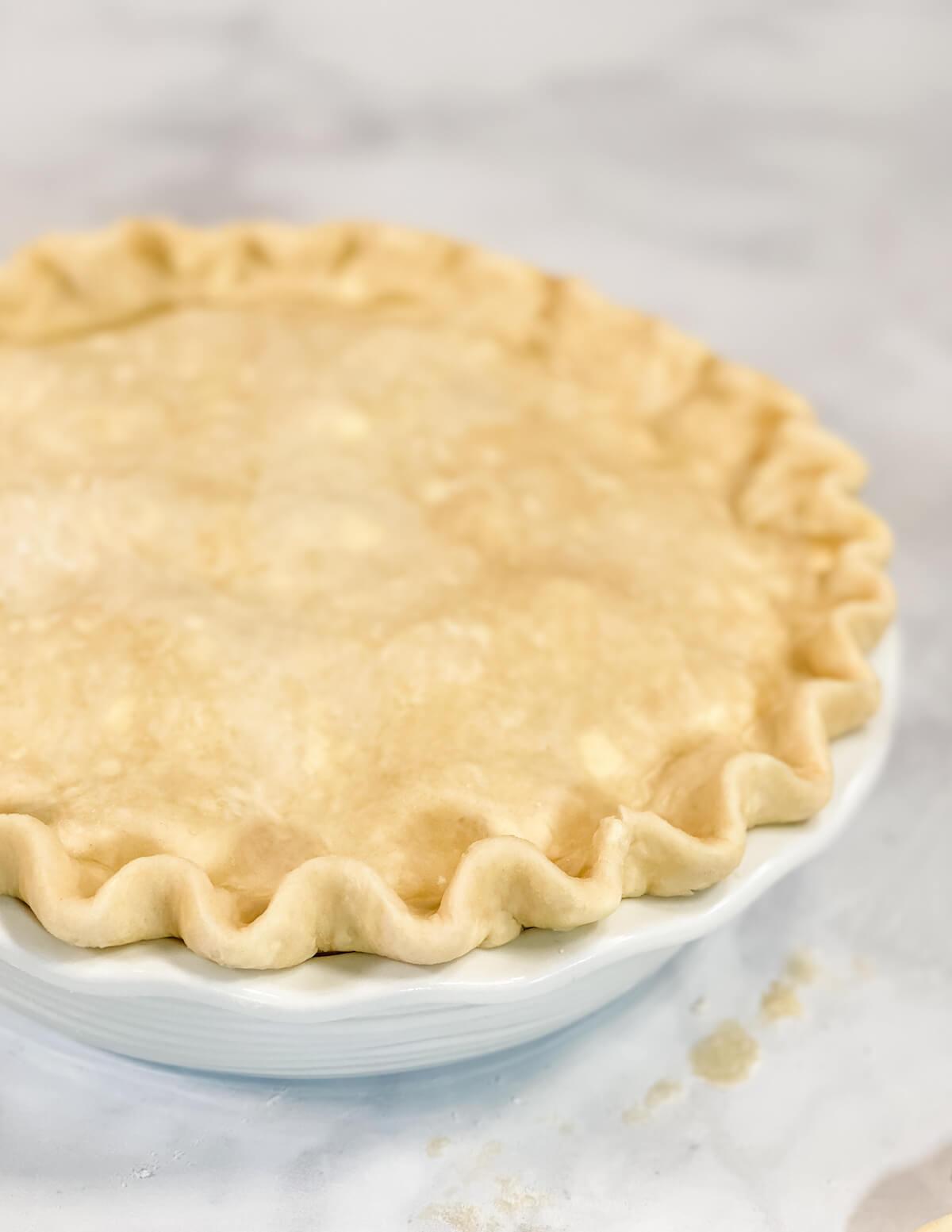 crimped pie crust in white pie plate