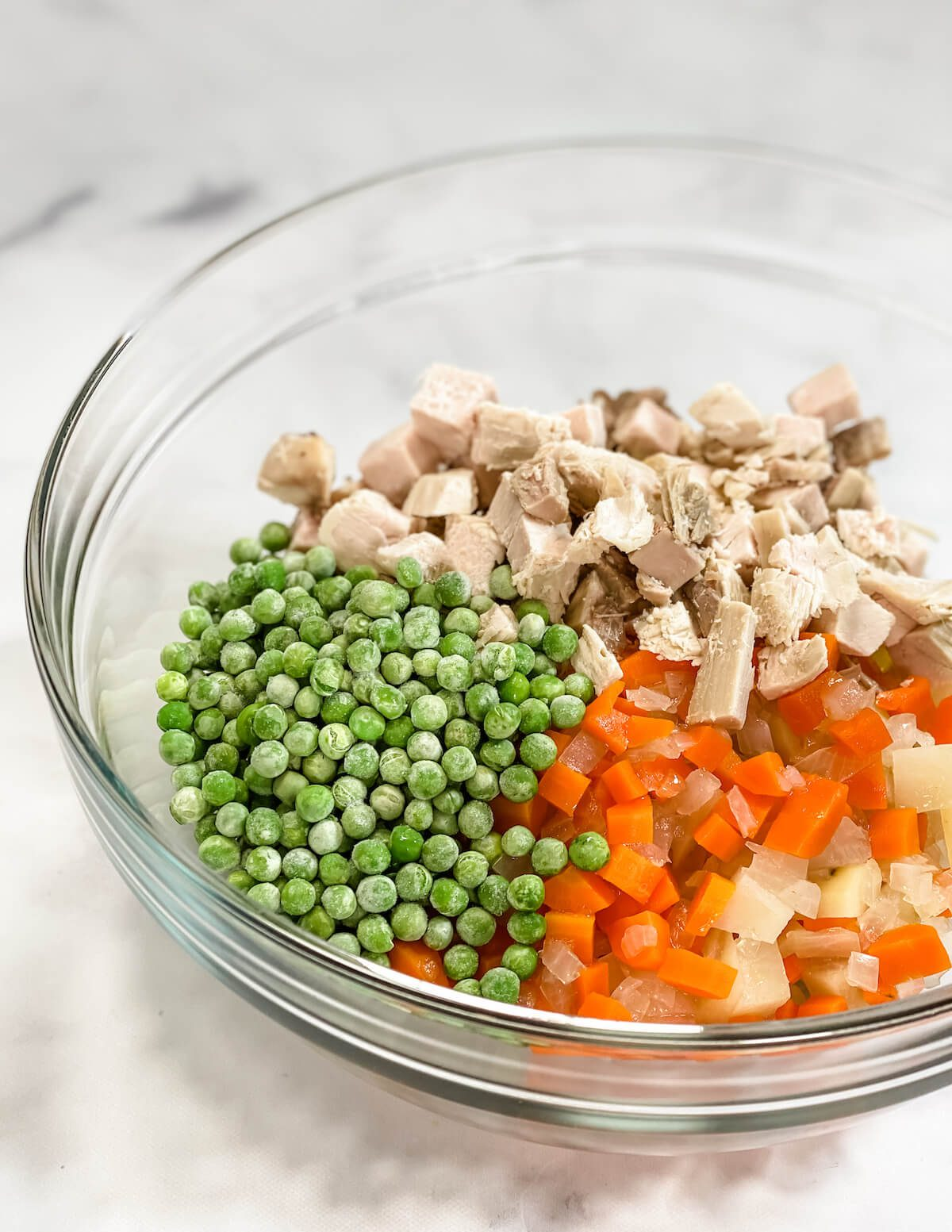 peas and carrots and turkey in mixing bowl