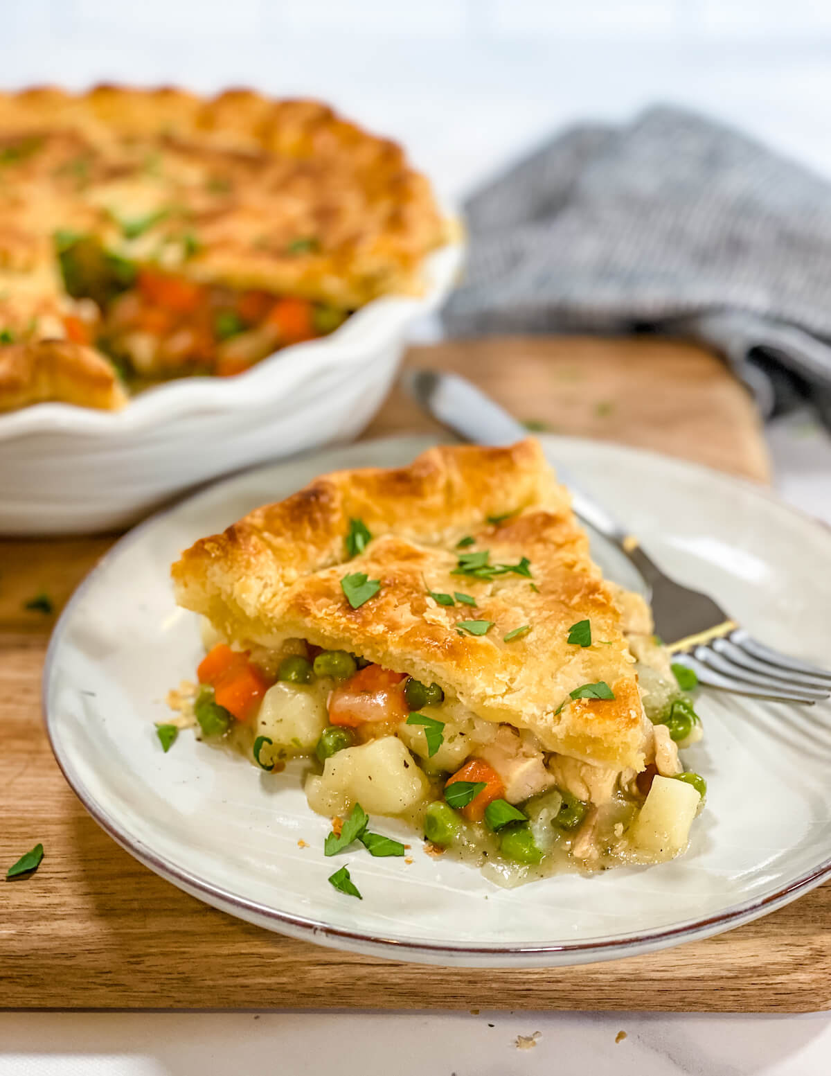 slice of homemade turkey pot pie on a plate with parsley