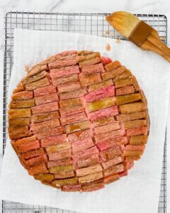 baked rhubarb cake getting brushed with syrup