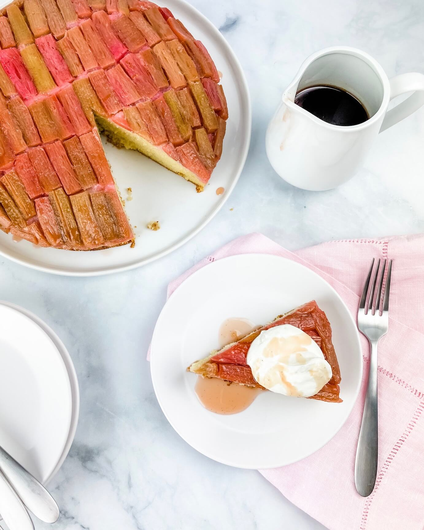 overhead picture of baked rhubarb cake with a slice out on a plate