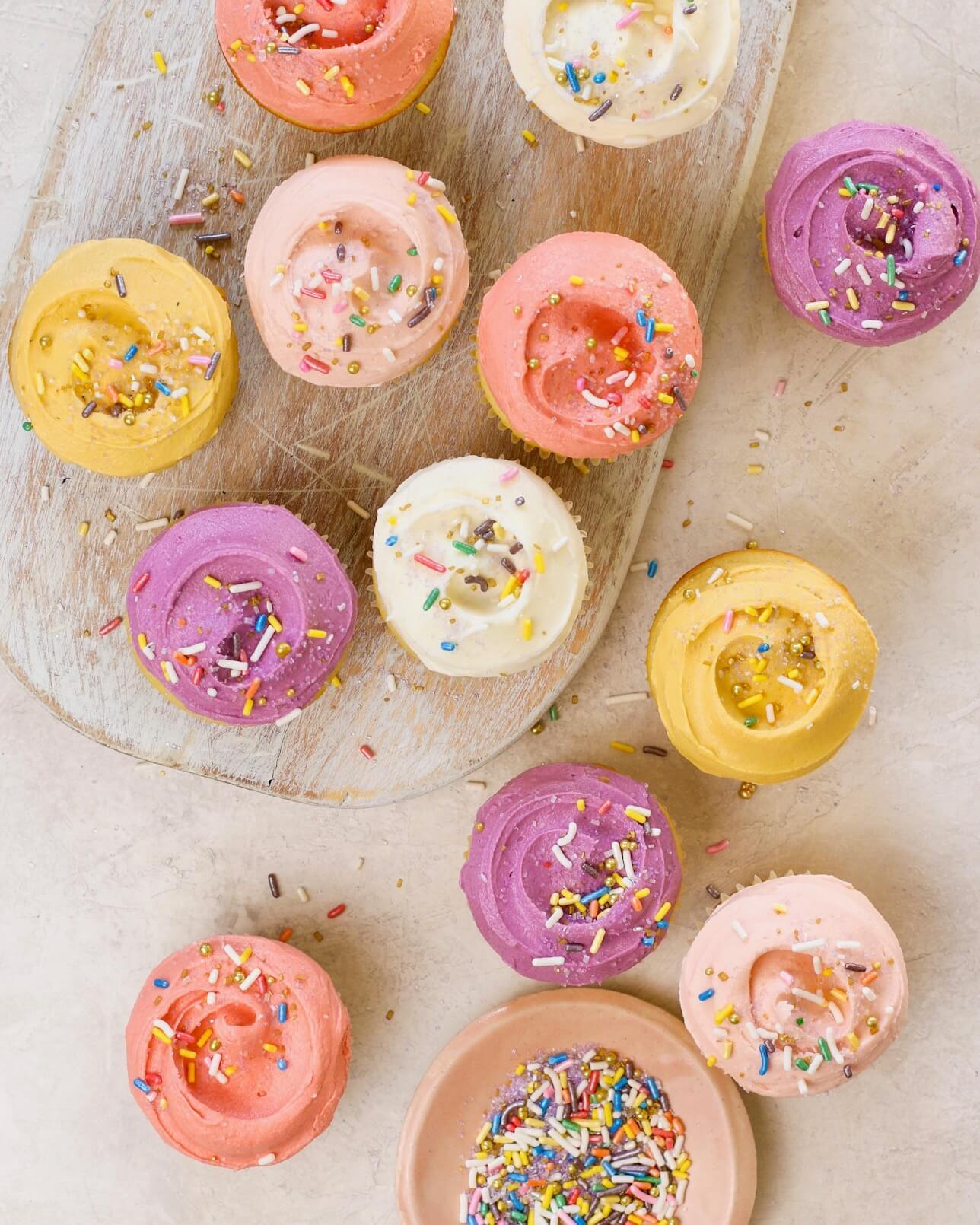 frosted birthday cupcakes on a cutting board with sprinkles