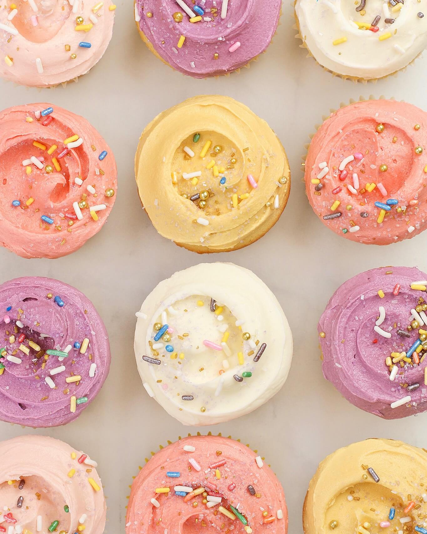 twelve birthday cake cupcakes in a row overhead with frosting and sprinkles