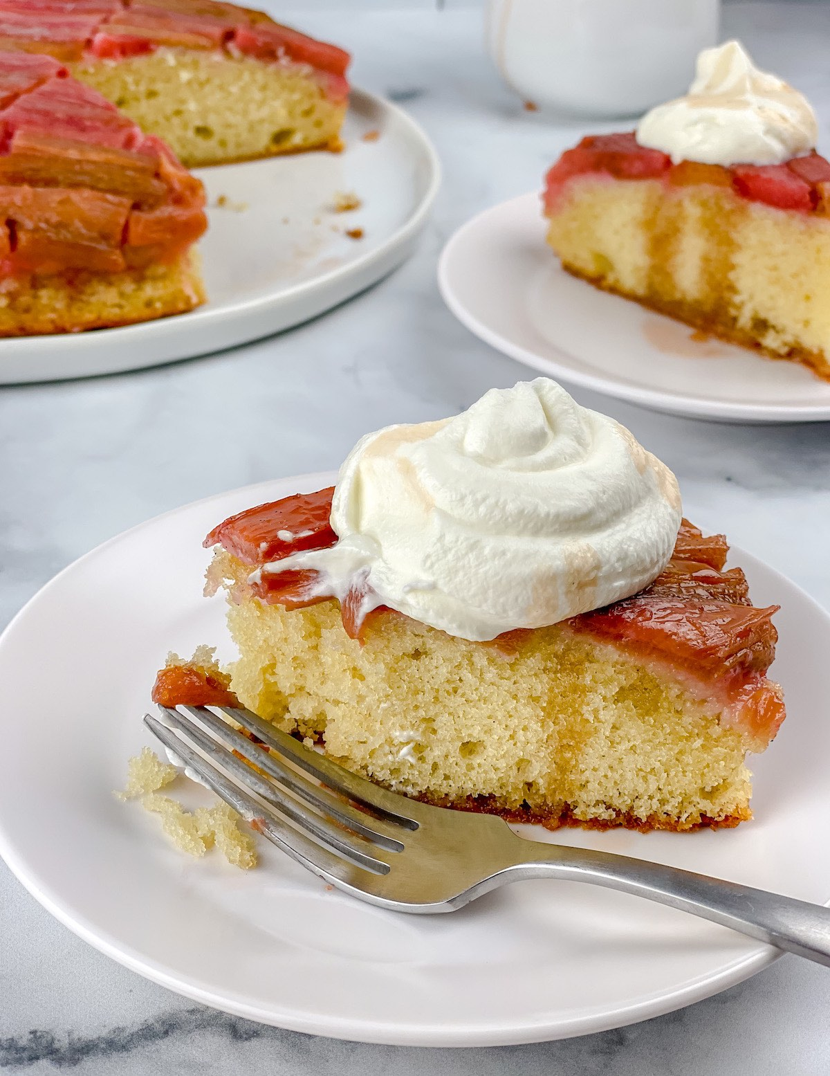 close up of rhubarb cake with a fork and messy cream
