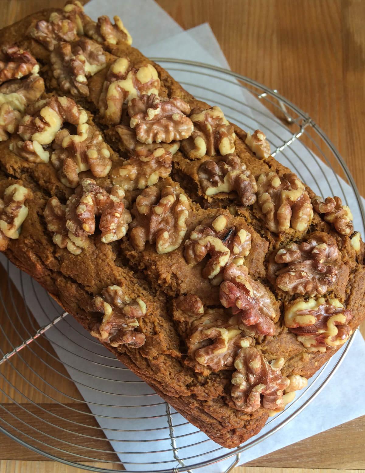 overhead of walnuts baked on a loaf of pumpkin bread