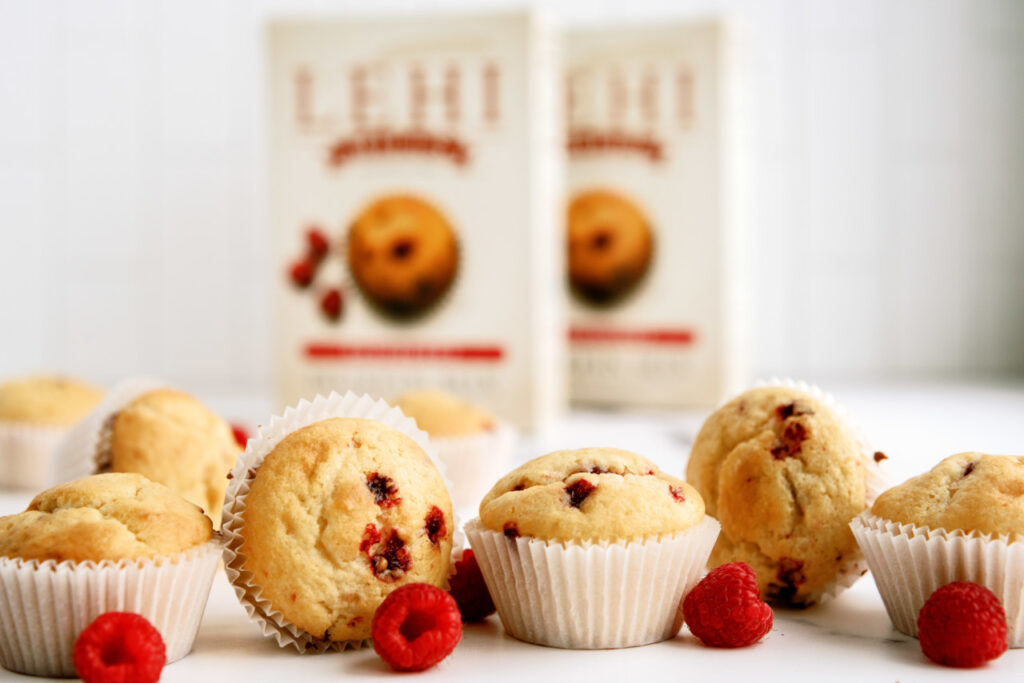 Close up view of baked Lehi Roller Mills berry muffins with muffin mix boxes in background