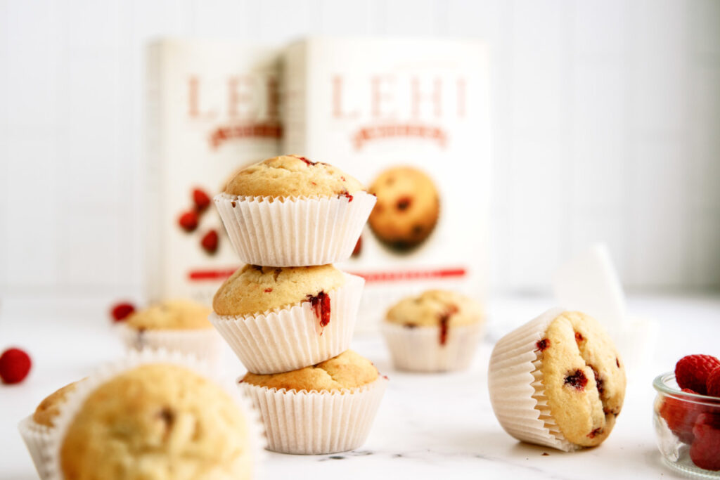 3 berry muffins stacked on top of one another with Lehi Roller Mills muffin mix boxes in the background